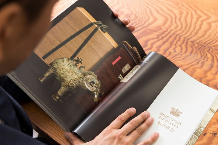 クリスティーズニューヨークでのオークションのカタログより。「鳳龍文羊觥(ほうりゅうもんようこう)」。後ろの2つの箱のうちの右側が、塗りをほどこしたいわゆる「藤田箱」で、藤田傳三郎が自身のコレクションのために製作したオリジナル。